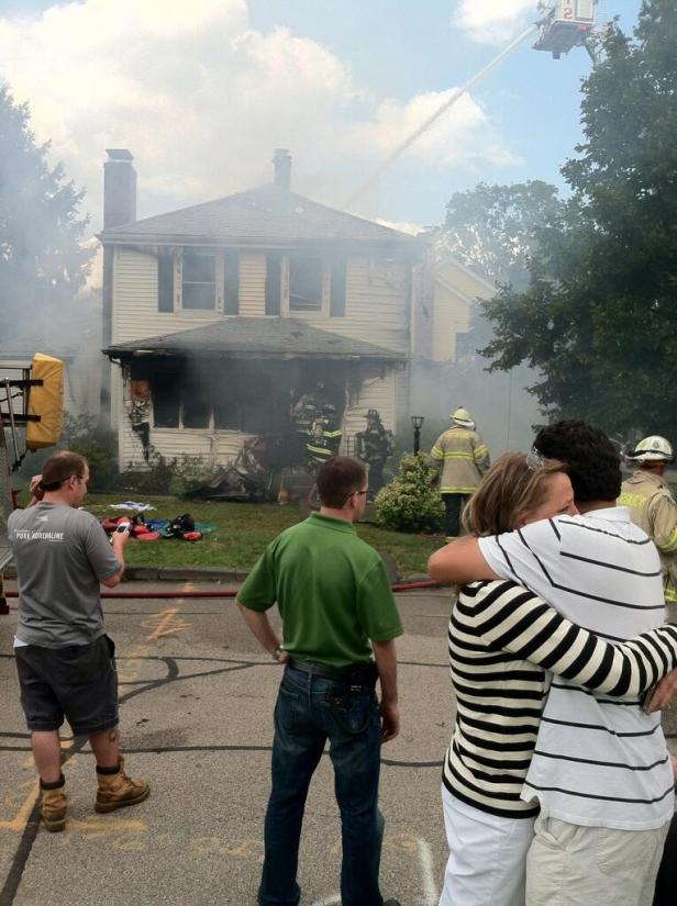 Neighbors hug as firefighters work to extinguish a house fire in August 2013